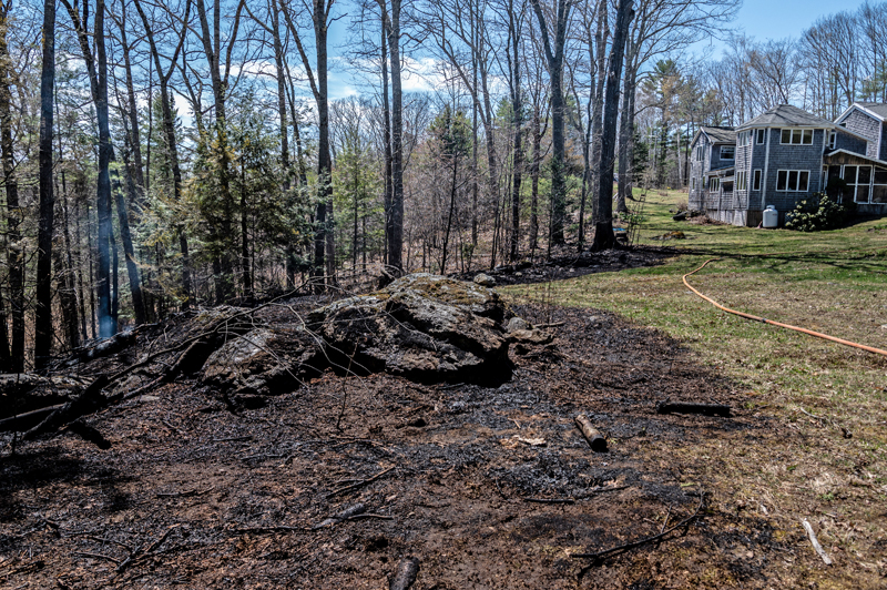 Charred land where a woods fire encroached on a yard in Somerville on Tuesday, April 27. The fire came within 100 feet of the house. (Bisi Cameron Yee photo)