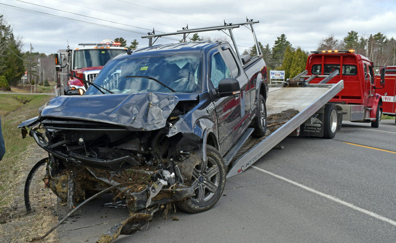 Hillside Collision Center tows a 2020 Ford F-150 out of a ditch on the side of Route 1 in Waldoboro on Sunday, April 18. The driver told police that he started choking on food while exiting the RSU 40 bus garage across the street and drove into the ditch. (Evan Houk photo)