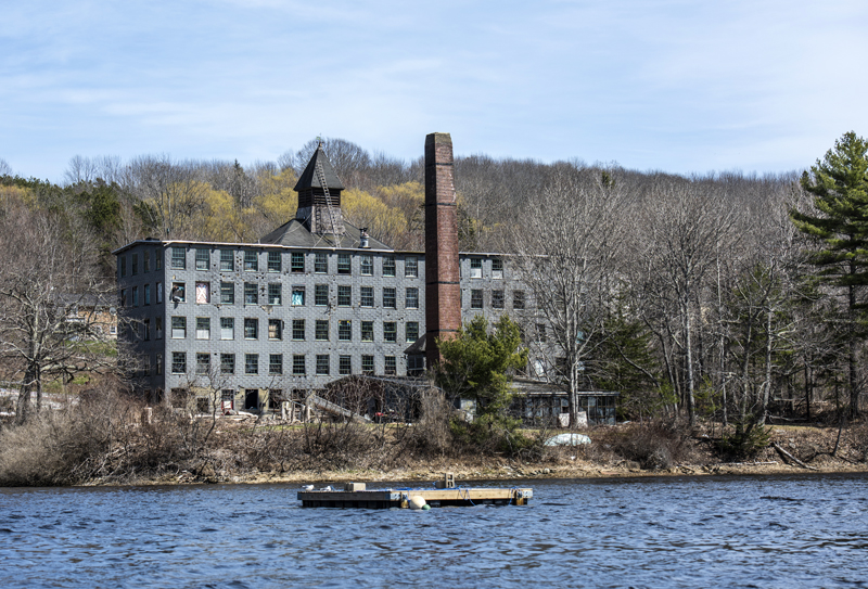 An upweller awaits deployment in the Medomak River in Waldoboro on Thursday, April 15, as the old Paragon Button Factory fills the shoreline behind it. (Bisi Cameron Yee photo)