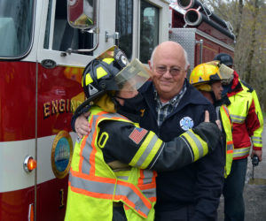 Waldoboro firefighter Marie Searles embraces Bristol Fire Chief Paul Leeman Jr. in Round Pond on Friday, April 30. Firefighters from around Lincoln County gathered to surprise Leeman and celebrate his retirement. (Maia Zewert photo)