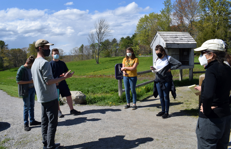 Pearce Kelley, of the Maine Mathematics and Science Alliance, left, discusses a mission on the STEMports augmented reality app with Great Salt Bay Community School students, his colleague Brittney Nickerson (second from right), and GSB enrichment specialist Alison Macmillan (right) at the Whaleback Shell Midden State Historic Site in Damariscotta on Wednesday, May 12. (Evan Houk photo)