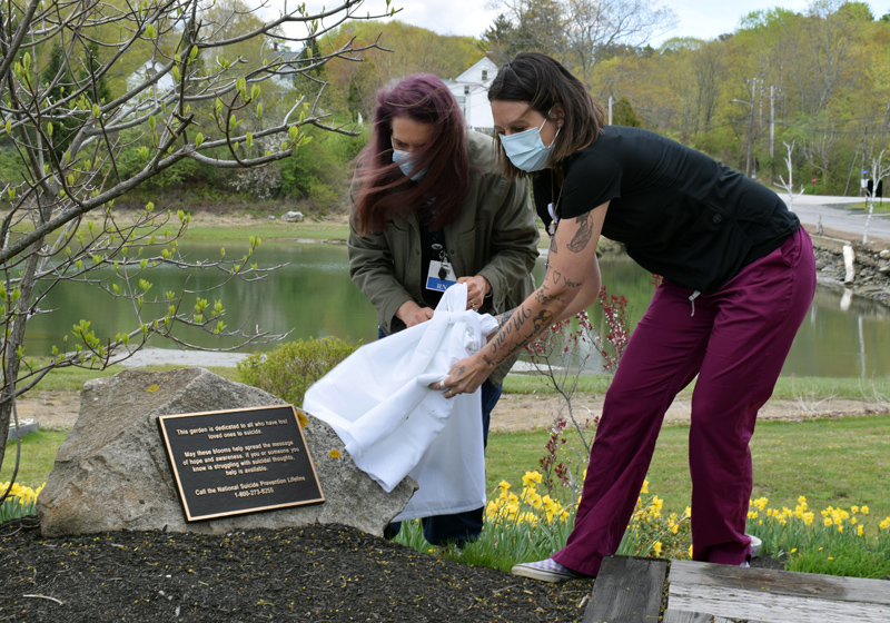 LincolnHealth employees Trudy DeLong (left) and Rebekah Oliver unveil a plaque on a stone in front of the suicide prevention awareness garden on the hospital's Miles Campus in Damariscotta during a dedication ceremony on Monday, May 10. (Evan Houk photo)