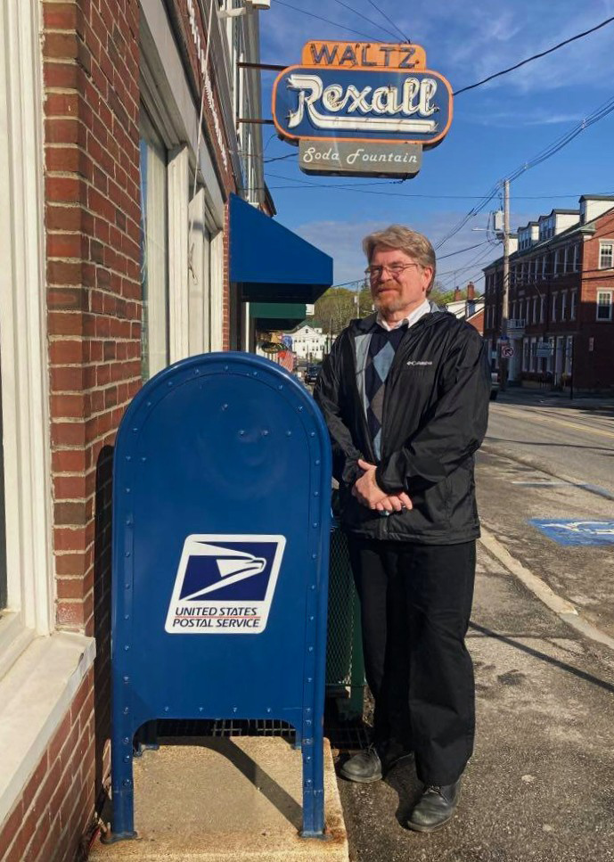 Recently retired Damariscotta Postmaster Tom Hutchins stands outside his office for the last 16 years. (Nettie Hoagland photo)