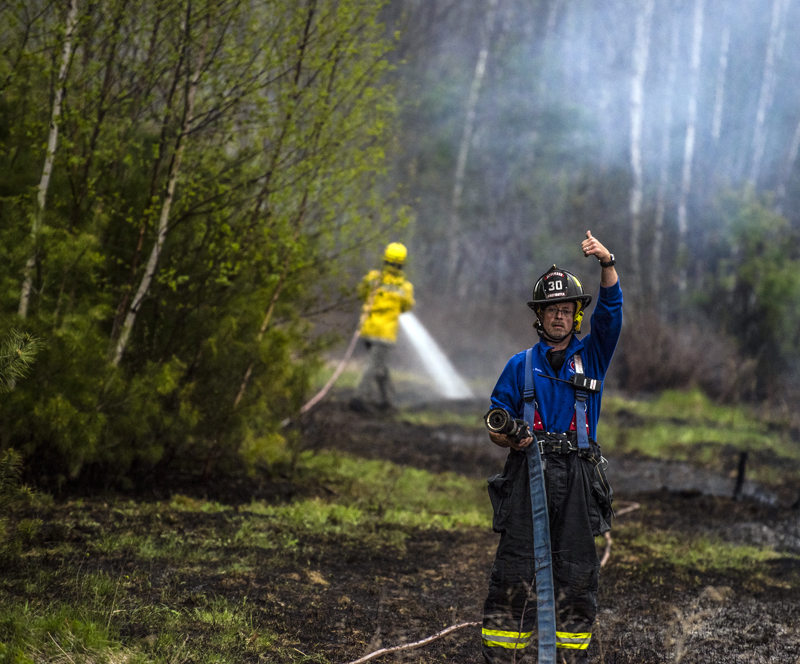 A firefighter gives a thumbs-up to start pumping water during a brush fire in Jefferson on Monday, May 3. (Bisi Cameron Yee photo)