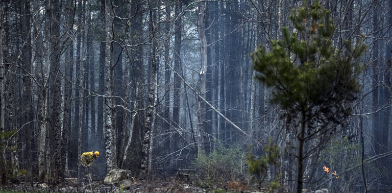 A firefighter moves through a woods fire in Jefferson on Monday, May 3. (Bisi Cameron Yee photo)