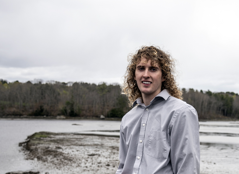 """Zak Melvin stands in front of the Medomak River in Waldoboro on Saturday, May 8. Melvin calls the river """"his safe place"""" where he can escape the stress of teaching and return to clamming, which he has done since he was 10. (Bisi Cameron Yee photo)"""
