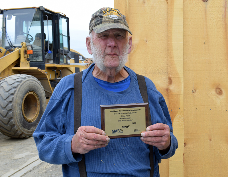 Eben Hunt holds a plaque recognizing N.C. Hunt for placing third in the Maine Association of Broadcasters' Best Campaign competition in 2019. Hunt voices the ads, but spends most of his days using the loader in the background to screen loam at the Jefferson lumberyard. (Evan Houk photo)
