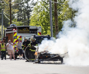 A family from Cushing watches as firefighters extinguish a fire on their utility trailer in Waldoboro on Wednesday, May 19. (Bisi Cameron Yee photo)