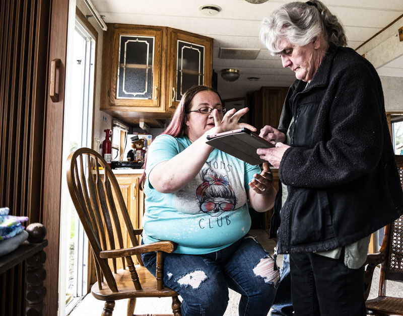 Rachel Lane helps her mother-in-law, Viola Stone, sign documents with her tablet in Waldoboro on May 4. Lane is helping Stone navigate the paperwok needed to bring a case in front of the town's appeals board. (Bisi Cameron Yee photo)