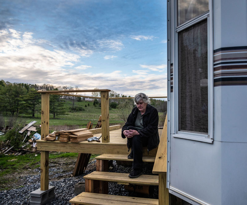 Viola Stone sits outside her trailer on the property she considers home in Waldoboro on May 4. The park model camper does not comply with the town's land use ordinance. (Bisi Cameron Yee photo)