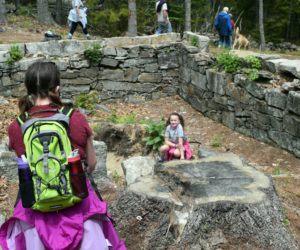 Shannon Taylor (left) photographs daughter Ori Taylor as she poses with a scavenger hunt item at the James Franklin Dunton home site in Westport Island on Sunday, May 23. (Nate Poole photo)