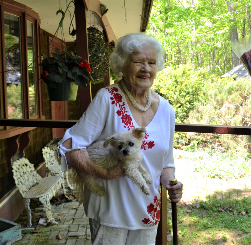 Bette Monfort holds the Boston Post Cane and her 10-year-old dog, Candy, at her home on Westport Island, Friday, May 21. The cane honors Monfort as the town's eldest resident. (Charlotte Boynton photo)