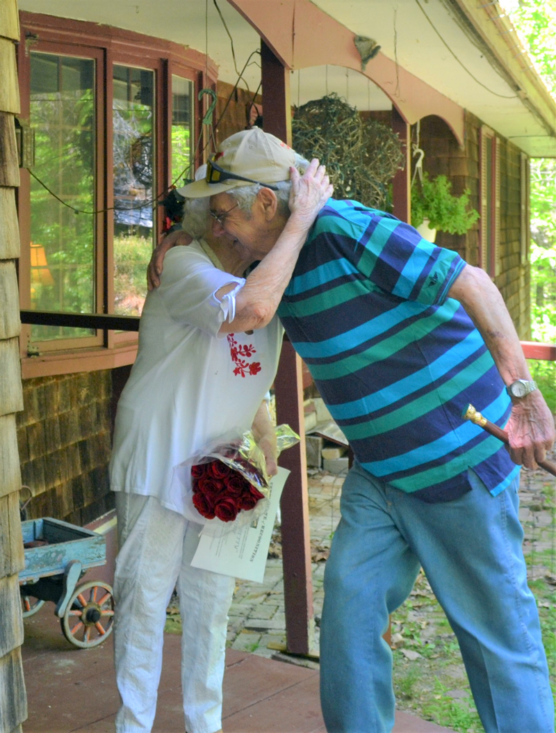 Bette Monfort gives Westport Island First Selectman George Richardson Jr. a hug at her home on the island, Friday, May 21. Richardson and Third Selectman Ross Norton presented Monfort with the town's Boston Post Cane and a dozen red roses. (Charlotte Boynton photo)