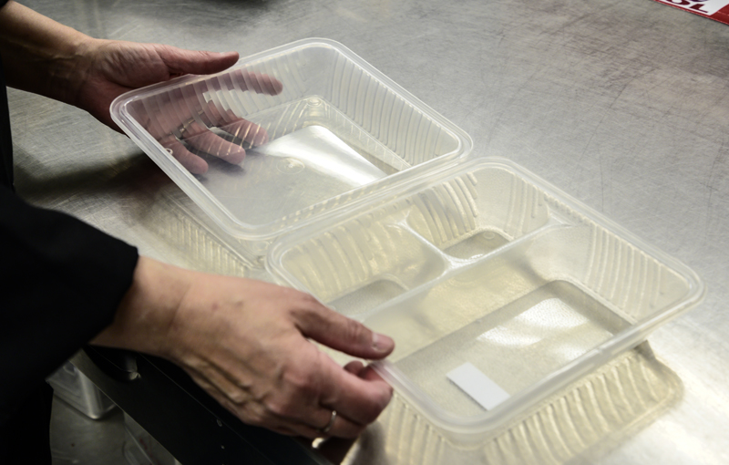 Vicki Dill demonstrates the reusable container Whitefield Elementary School uses to serve to-go lunches. Judges at Maine's Farm to School Cook-off were impressed by the sustainable packaging. (Bisi Cameron Yee photo)