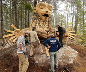 A crew from Bristol Marine assists with the installation of a giant troll at Coastal Maine Botanical Gardens.