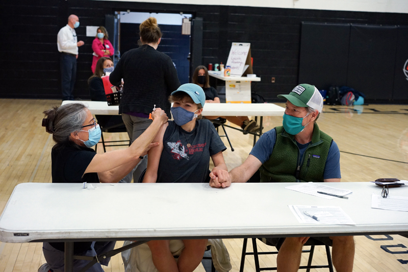 Great Salt Bay Community School eighth grader Tessa McNamara (center) holds hands with her father, Jay McNamara (right), while receiving a vaccination from  LincolnHealth nurse and Lincoln Academy parent Angela Russ during a clinic at the high school on Tuesday, May 18.