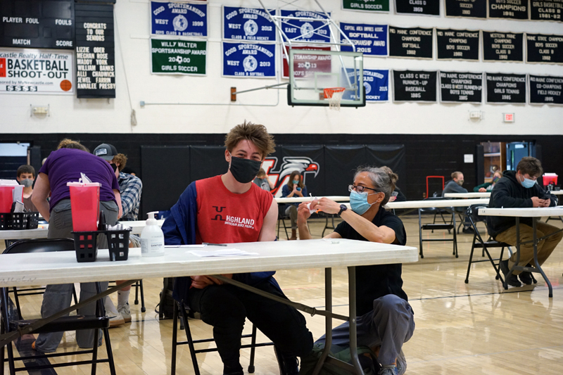 Lincoln Academy ninth grader Jonas Stepanauskas gets vaccinated by LincolnHealth registered nurse Angela Russ at the LA vaccination clinic on Tuesday, May 18.