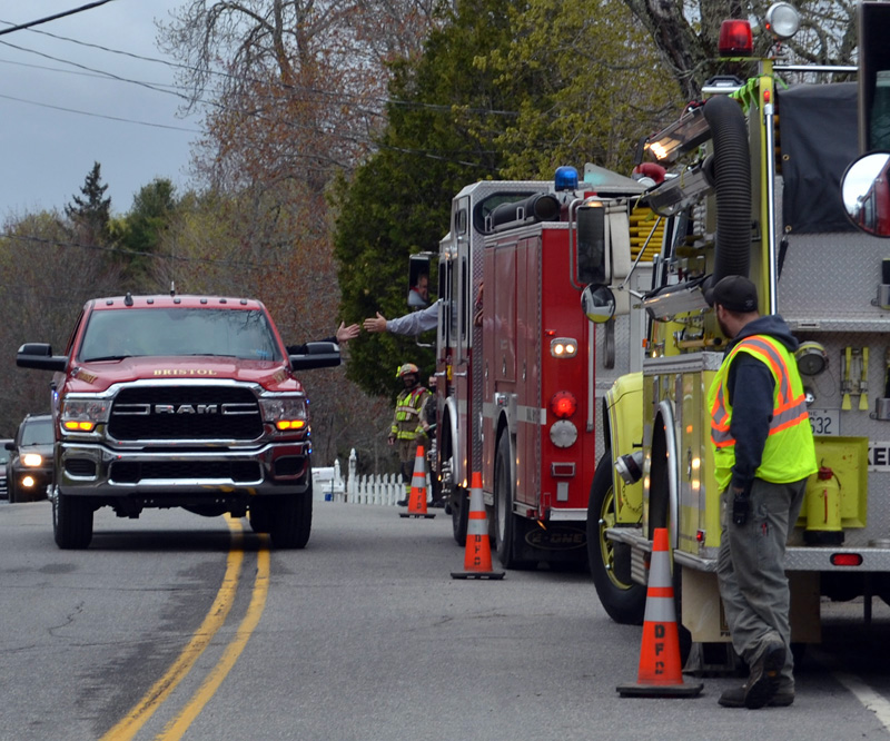 Bristol Fire Chief Paul Leeman Jr. reaches out to high-five Jefferson Fire Chief Walter Morris while driving along Route 32 in Round Pond, Friday, April 30. Firefighters from around the county organized a surprise retirement celebration for Leeman. (Maia Zewert photo)