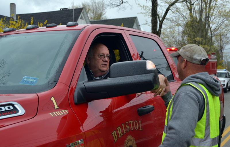Bristol Fire Chief Paul Leeman Jr. (left) shakes hands with Damariscotta 2nd Assistant Fire Chief Josh Pinkham while driving through Round Pond village on Friday, April 30. (Maia Zewert photo)