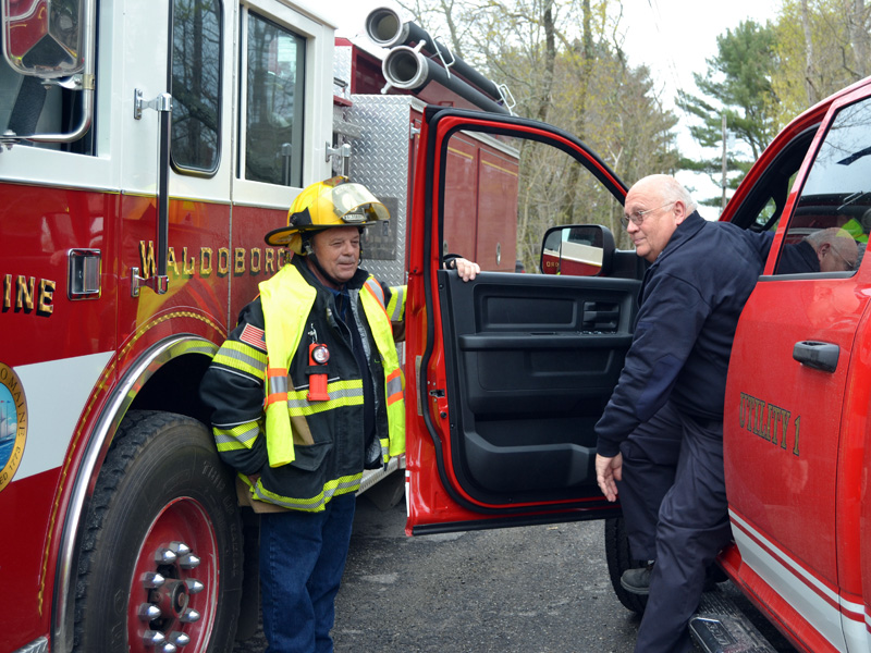 Waldoboro firefighter Billy Bragg holds the door for Bristol Fire Chief Paul Leeman Jr. as he arrives at the Round Pond fire station on Friday, April 30. (Maia Zewert photo)