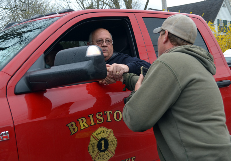 Bristol Fire Chief Paul Leeman Jr. shakes hands with Capt. Chris Hilton, of the Damariscotta Fire Department, during a surprise celebration of Leeman's retirement on Friday, April 30. Leeman was overcome with emotion as he was congratulated by a line of firefighters and other emergency workers while driving to the Round Pond station. (Maia Zewert photo)