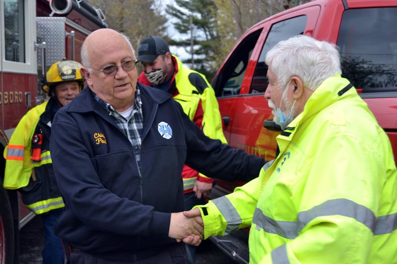 Bristol Fire Chief Paul Leeman Jr. (left) shakes hands with Bremen Selectman Hank Nevins in Round Pond on Friday, April 30. (Maia Zewert photo)