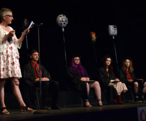 """Central Lincoln County Adult Education instructor Elizabeth Potter reads a poem by Edgar Guest about perseverance, """"It Couldn't Be Done,"""" before toasting to the 2020-2021 graduates of the program during a ceremony at the Lincoln Theater on Tuesday, June 8. From left: Elizabeth Potter, Zachary Baker, Emmalie Blanchard, Honora Boothby, and Norbert Ferrero. (Evan Houk photo)"""