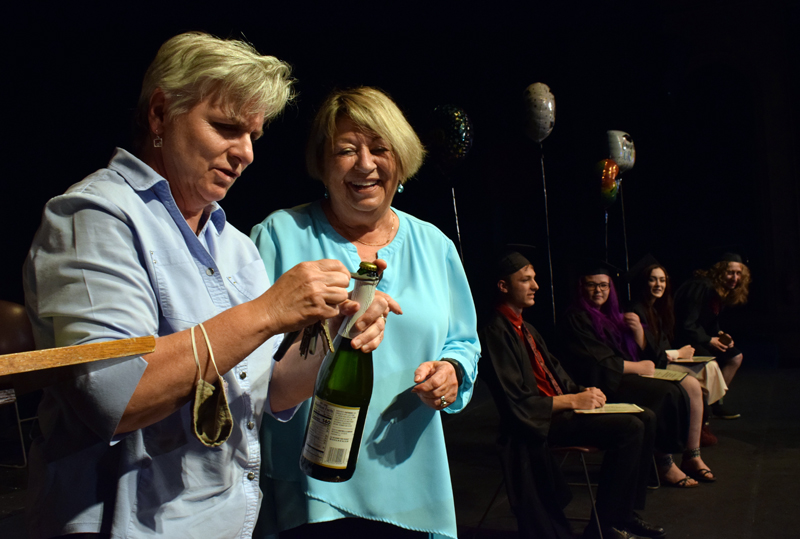 Central Lincoln County Adult Education instructor Bonnie Merrill (left) works to open a bottle of sparkling juice for a toast to the class of 2020-2021 as Director Pam Sperry and graduates look on during a graduation ceremony at the Lincoln Theater on Tuesday, June 8. (Evan Houk photo)