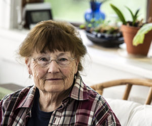Julie Babb sits in the sunroom at her home in Damariscotta on Tuesday, June 8. Babb is known for the realism and attention to detail she brings to her paintings of birds. (Bisi Cameron Yee photo)