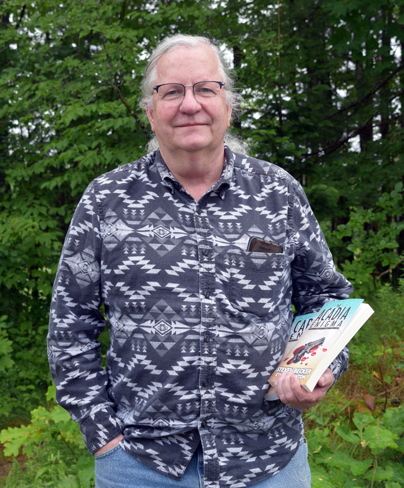 """Nobleboro resident Chuck Benton holds his two books, """"The Acadia Enigma"""" and """"The Cape Cod Enigma."""" Benton began writing with his bestselling co-author, Steven Becker, in 2020. (Nate Poole photo)"""