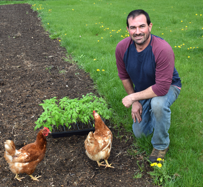 Josh Hatch poses in his garden with the chickens that he raises on his property in Nobleboro on May 6. Hatch did not seek reelection to the Nobleboro School Committee this year after 15 consecutive years of service. (Evan Houk photo)
