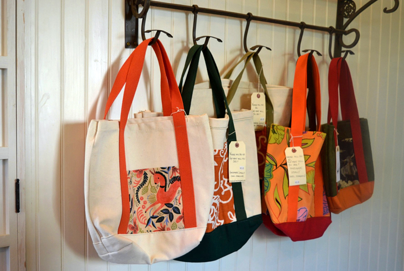 Carol Hoagland, of Bristol, sells her handmade canvas and leather bags at Kneaded Provisions on Rutherford Island. Manager Jennifer Keegan encourages local artists and artisans to display and sell their work at the business. (Nettie Hoagland photo)