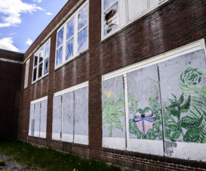 Graffiti covers boarded-up windows of the former A.D. Gray School in Waldoboro on May 14. Voters may decide the building's fate Tuesday, June 8. (Bisi Cameron Yee photo)