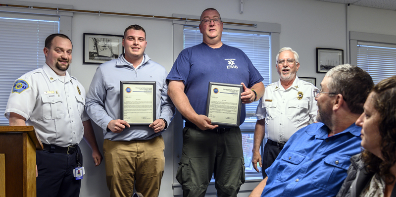 Waldoboro Emergency Medical Services Deputy Director Derek Booker (left) and EMS director Richard Lash (right) honored Emergency Medical Technicians Kobe Lincoln and Justin Hills with citations for their service to a resident in cardiac arrest in Waldoboro on Tuesday, June 22. (Bisi Cameron Yee photo)
