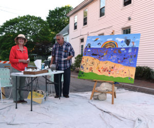 Artist Celia Ludwig (left) and her husband Stephen stand at the community mural station at the Wiscasset Art Walk on Thursday, June 24. Ludwig came up the with the idea for the mural and donated the canvas. (Nate Poole photo)
