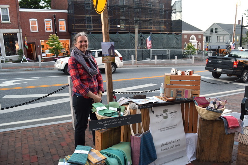 Hilary Crowell stands at her table at the Wiscasset Art Walk on Thursday, June 24. Crowell owns The Cultivated Thread, a Midcoast handwoven goods business in Bath. (Nate Poole photo)