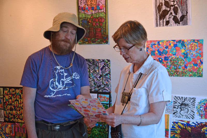 Visiting artist Seth Bond Perry (left) and Wiscasset Art Walk co-founder Lucia Droby discussing some of Perry's work in the Hasenfus Gallery on Thursday, June 24. (Nate Poole photo)