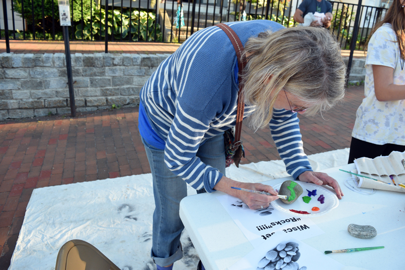 Margot Stiassni-Sieracki paints a mountain scene at the rock-painting station at the Wiscasset Art Walk on Thursday, June 24. (Nate Poole photo)