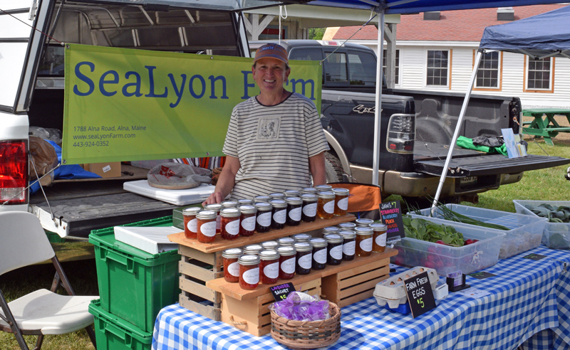 Marcia Lyons, president of the Wiscasset Farmers' Market, stands in her tent at the market on Wednesday, June 2. Lyons co-owns SeaLyon Farm, of Alna, with her husband Don. (Nate Poole photo)