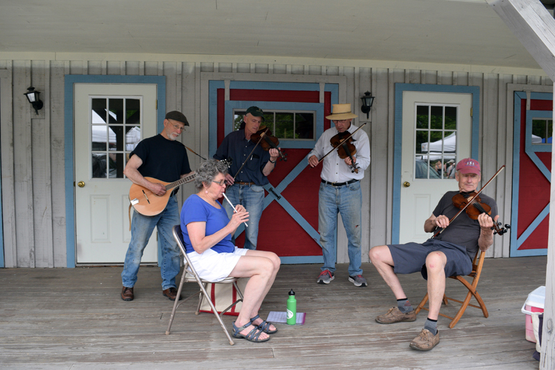 Folk musicians perform on the front porch of the Maine Tasting Center at the Wiscasset Farmers' Market on Wednesday, June 2. (Nate Poole photo)