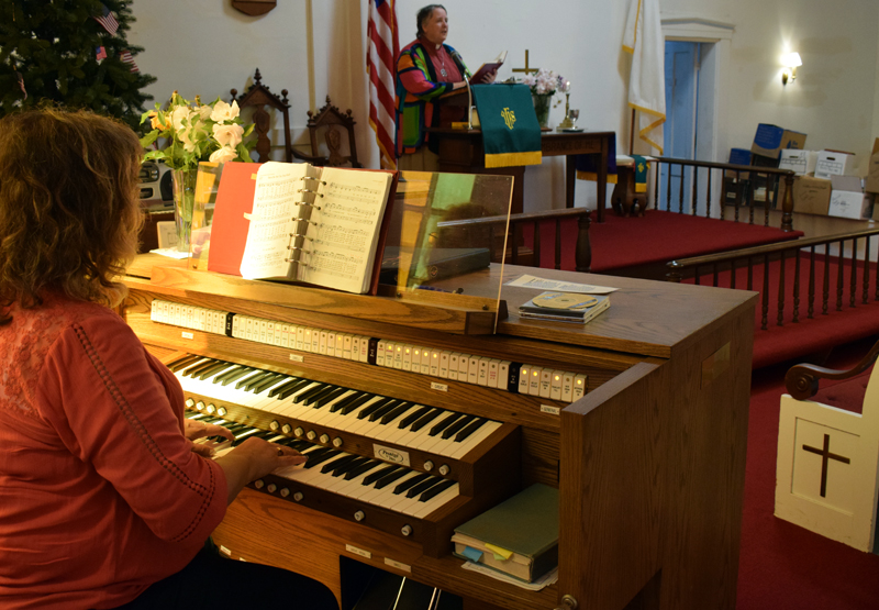 Organist Tricia Demers plays a hymn as Pastor Kelly Harvell leads the congregation in song during the final service of the Round Pond United Methodist Church on Sunday, June 27. About 43 people ended to celebrate and reflect on the church's 168-year history. (Evan Houk photo)
