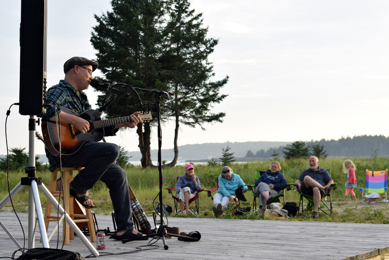 Jud Caswell plays a song on his guitar and sings at Pemaquid Beach during a fundraiser for the reconstruction of the Seagull Shop on Monday, July 12. More than $3,440 was raised during the event and the shop's owners say they plan to reopen by late July or August. (Evan Houk photo)