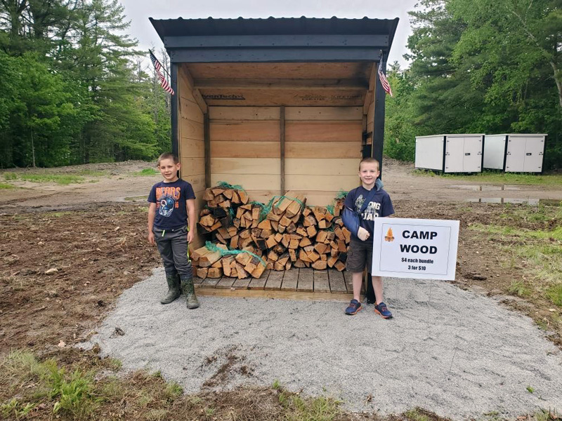 Zachary Hoppe and Ryan Parson stand in front of their camp firewood stand. The 7-year-olds plan to keep the stand open through Labor Day. (Photo courtesy Jessica Hoppe)