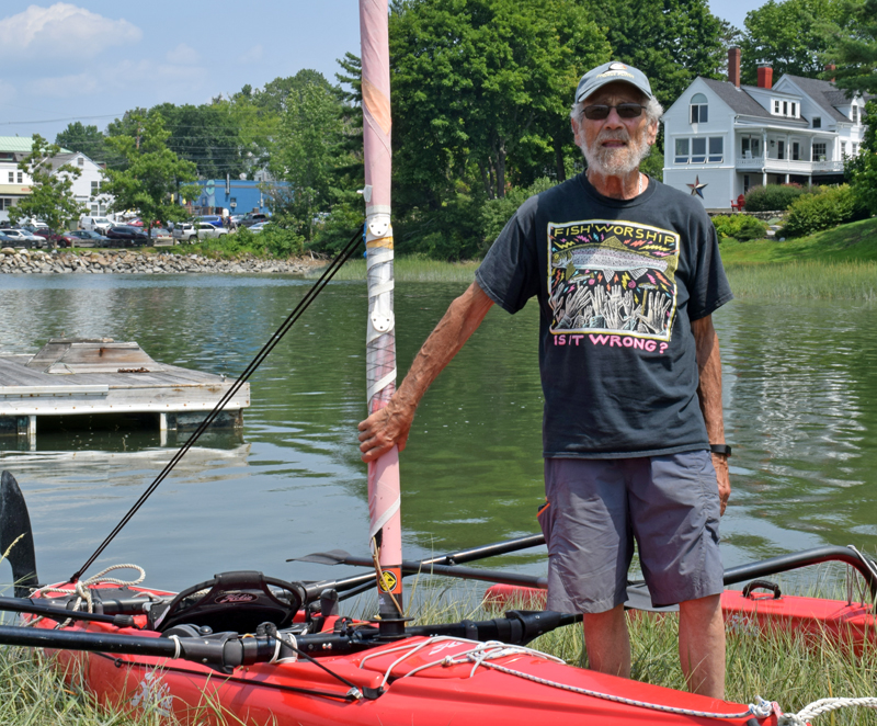 """Michael """"Mike"""" Herz stands by his trimaran sailing vessel at his home on the Damariscotta River on Tuesday, July 27. Herz has sailed all over the world and continues to sail and stand-up paddleboard in the river. (Evan Houk photo)"""