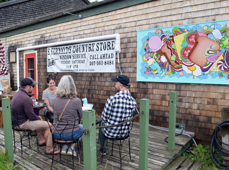 Diners enjoy a meal outside of S. Fernald's Country Store in Damariscotta on Friday, June 25. The store reopened to walk-in traffic on Tuesday, June 22, and sandwiches will continue to be available by window service on the opposite end of the building. (Evan Houk photo)