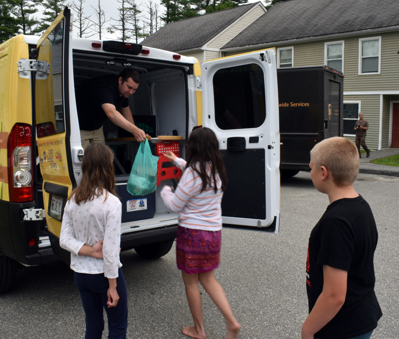 """Lee Emmons, summer meals coordinator for Healthy Lincoln County, hands out prepackaged meals to children at the Ledgewood Court apartments in Damariscotta on Thursday, July 15. The stop is one of five mobile sites that is visited by """"Lulu the Lunch Wagon"""" each Tuesday and Thursday throughout the summer to deliver free meals to kids. (Evan Houk photo)"""