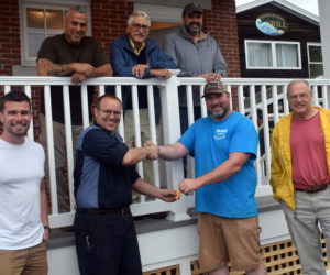 Robert Mattes, of Rockport-based Phi Builders + Architects, hands over the keys for the newly completed Damariscotta public restrooms to Damariscotta Board of Selectmen Chair Daryl Fraser on Friday, July 2. Front row, from left: Tom Mattes, of Phi Builders; Fraser; Robert Mattes; and Damariscotta Town Manager Matt Lutkus. Back row, from left: Charlie Frattini, of Phi Builders; architect George Parker; and Dan Phelps, of Damariscotta-based Phelps Architects. (Evan Houk photo)