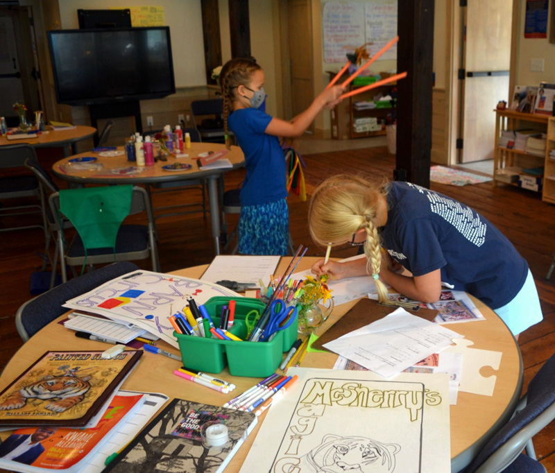 A camper designs a poster for the circus extravaganza during the Under the Big Top camp at the Merry Barn. (Nettie Hoagland photo)
