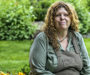 Bayard Littlefield sits among the flowers and greenery in one of the gardens she plans and tends in Bremen on Monday, July 19. (Bisi Cameron Yee photo)