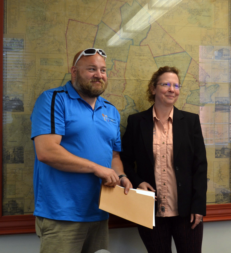 Lincoln County Communications Director Tara Doe presents the Maine EMS for Children Stork Award to Lincoln County dispatcher Josiah Winchenbach during the Lincoln County Board of Commissioners meeting on Tuesday, July 20. (Charlotte Boynton photo)
